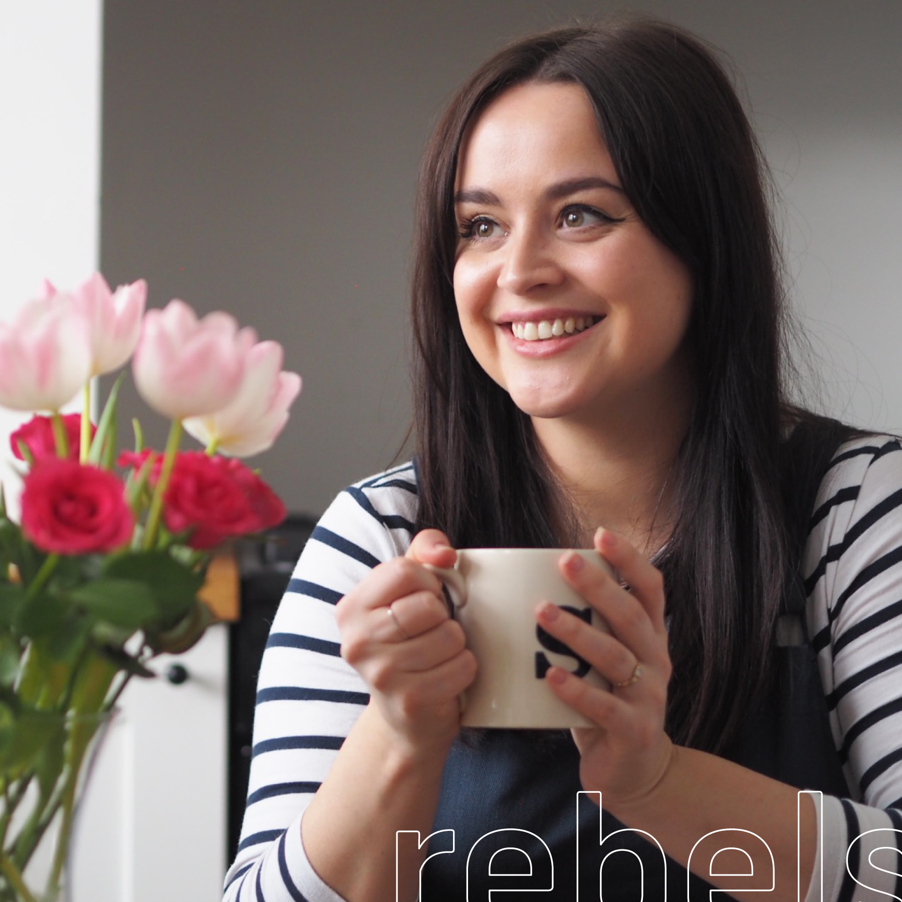Sophie Cliff is sitting in front of a white wall, smiling, and looking off camera to the left. She is wearing a white shirt with blue stripes underneath what appears to be a dark blue denim overall. She holding a white mug with the initial S on it in both hands. To the left of the image is a flower bouquet in a vase with dark pink roses and white and light pink tulips.